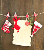 Blank sheet with Christmas decor hanging on grey wooden wall — Stock fotografie