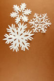 Beautiful paper snowflakes on brown background — Stock Photo