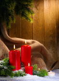 Candles and Christmas decoration on wooden background — Stock Photo