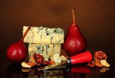 Cheese with mold and red pears with nuts on brown background close-up — Stock Photo