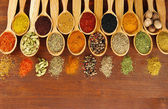 Assortment of spices in wooden spoons on wooden background — Stock Photo