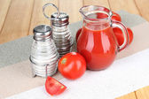 Tomato juice in glass jug, on wooden background — Stock Photo