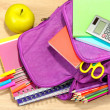 Purple backpack with school supplies on wooden background — Stock Photo #37940189