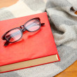 Composition with old book, eye glasses and plaid on wooden background — Stock Photo #37940237