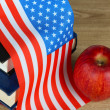 Composition of American flag, books and apple on wooden table background — Stock Photo #37942335