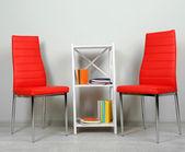 美しいインテリアがモダンな色の椅子、壁の背景上の木製のスタンドの本 — ストック写真
