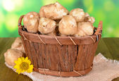 Topinambur roots in wooden basket on table on bright background — Stock Photo