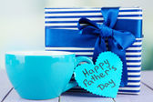 Happy Fathers Day tag with gift box and cup, on wooden table, on light background — Stock Photo