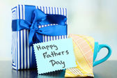 Happy Fathers Day tag with gift boxes, cup and tie, on wooden table, on light background — Stock Photo