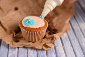 Confectioner decorating tasty cupcake with butter cream, on color wooden background — Stock Photo