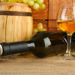 Composition of wine,box and grapes on wooden barrel on table on brick wall background — Stock Photo
