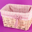 Wicket basket with pink fabric and bow, on color background — Stok Fotoğraf #37956253