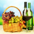 Ripe grapes in wicker basket, bottles and glass of wine, on bright background — Stock Photo