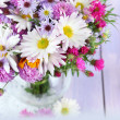 Wildflowers in glass vase on napkin on wooden table — Stock Photo