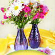Wildflowers in glass vases on table on light background — Stock Photo