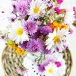 Wildflowers in glass vase on wicker tray on wooden table — Stock Photo