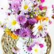 Stock Photo: Wildflowers in glass vase on wicker tray on wooden table