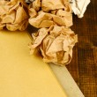 Stock Photo: Crumpled paper balls with notebook on table close up