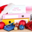 Stock Photo: Table with office supplies and Christmas tinsel on bright background