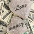 Stock Photo: Love and money concept. Heart-shaped stone and Americcurrency close up.