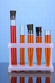 Tubos de ensayo con una solución de colorido en primer plano de fondo azul — Foto de Stock
