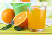 Glass of juice, citrus press and ripe orange on green wooden table — Stock Photo