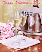 Champagne and glasses on round table on cloth background — Stock Photo