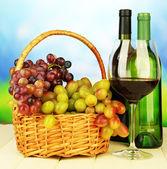 熟したブドウ枝編み細工品バスケット、ボトル、明るい背景上のワインのガラス — ストック写真