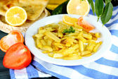 Ruddy fried potatoes on plate on tablecloth close-up — Stock Photo