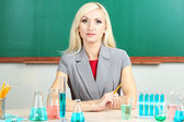 Chemistry teacher sitting at table on blackboard background — Stock Photo