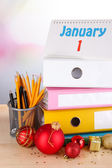 Table with office supplies and Christmas tinsel on bright background — Stock Photo