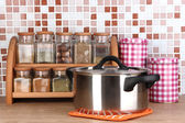 Pot and spices in kitchen on table on mosaic tiles background — Stock Photo