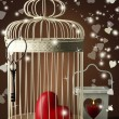Stock Photo: Heart in decorative cage on wooden table, on brown background