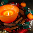 Stock Photo: Burning candle with Christmas decorations on color wooden background