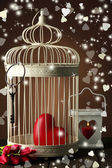 Heart in decorative cage on wooden table, on brown background — Stock Photo