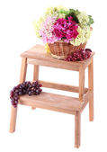 Wicker basket with flowers and fruits, on small wooden ladder, isolated on white — Stock Photo