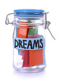 Dreams written on color paper in glass jar, isolated on white — Stock Photo