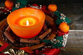 Burning candle with Christmas decorations on color wooden background — Стоковое фото