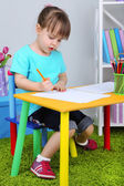 Little girl draws sitting at table in room — Photo