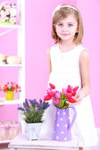 Beautiful little girl and stand with flowers on pink background — Stock Photo