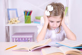 Little girl sitting at desk in room — Stock Photo