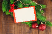 Christmas card on fir branch on wooden background — Stockfoto