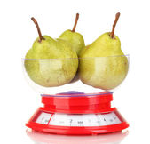 Ripe pears in kitchen scales isolated on white — Stock Photo