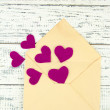 Beautiful old envelope with decorative hearts on wooden background — Stock Photo #38105575