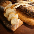 Much bread on wooden board — Stock Photo #38101057