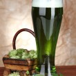Stock Photo: Glass of green beer and hops, on wooden table