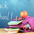 Purple backpack with school supplies on wooden table on green desk background — Stock Photo #38102205