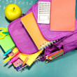 Purple backpack with school supplies on green desk background — Stock Photo #38102207