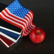 Composition of American flag, books and apple on wooden table background — Stock Photo #38104513