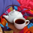 Cup and teapot on wooden stand and scarf on bed close up — Stock Photo